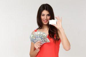 紙幣とカードを持つ女性